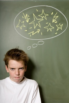 Picture of a boy standing in front of a chalkboard who looks angry and frustrated.