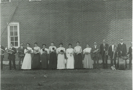 Early Lake City Band taken in front of Ramsey Hall; tin siding with fake bricks painted on; photo by C. E. Wright