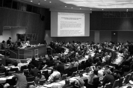 Disability Convention negotiations in Conference Room 4, showing many delegates seated in rows and chair and secretaries on stage in front of room, also a screen with some of the text at the right front.