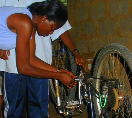 A woman learns to repair her bicycle in Ghana, Africa through a Village Bicycle Project repair workshop