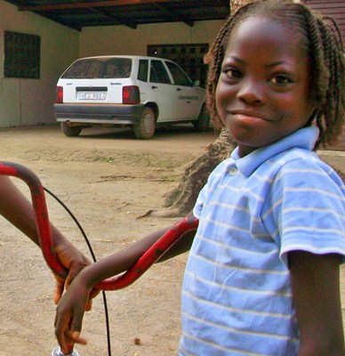 A girl poses happily with her new bike in Sierra Leone, Africa. She got her bike and learned to ride from Village Bicycle Project.